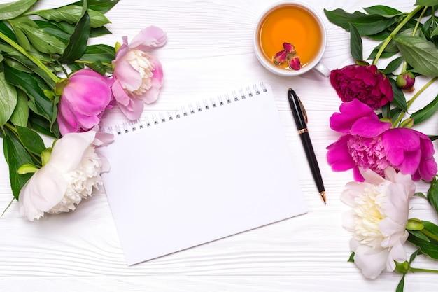 Leeres notizbuch mit platz für text, stift, eine tasse tee und pfingstrosenblumen auf einem weißen hölzernen hintergrund.