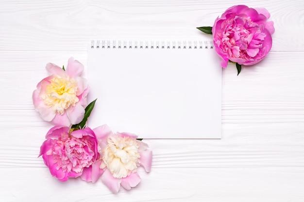 Leeres notizbuch mit platz für text- und pfingstrosenblumen auf einem weiß