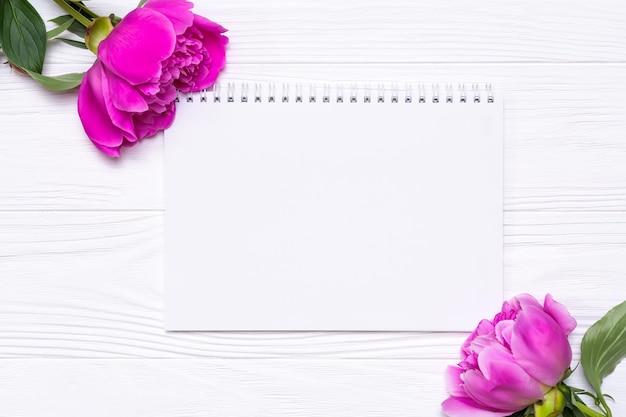 Leeres notizbuch mit platz für text- und pfingstrosenblumen auf einem weißen hölzernen hintergrund. von oben betrachten.