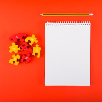 Leeres notizbuch mit puzzlespielen auf roter tabelle