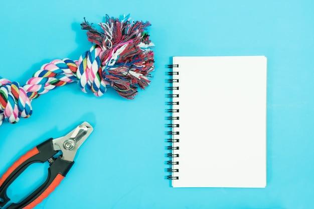Leeres notizbuch mit seil, schüsseln und gummispielzeug auf blauem hintergrund