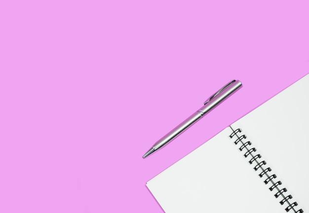 Leeres notizbuch mit stift auf rosa hintergrund. geschäfts- oder bildungskonzept.