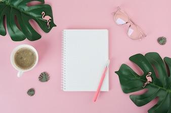 Leeres Notizbuch mit Stift auf rosa Tabelle
