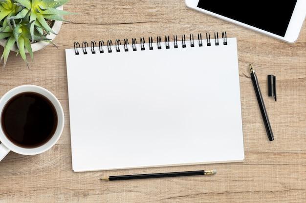 Leeres notizbuch mit stift ist auf hölzerne schreibtischtabelle. draufsicht, flach zu legen.