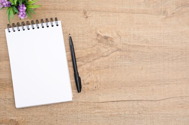 Leeres notizbuch mit stift ist auf hölzerne schreibtischtabelle.