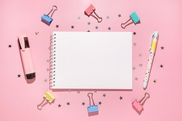 Leeres notizbuch mit stift, marker, clips und konfettisternen gießt auf pastellrosa hintergrund, draufsicht. flach liegen. urlaub, gruß oder gute nachrichten konzept. modellvorlage. ansicht von oben. leerer notizblock