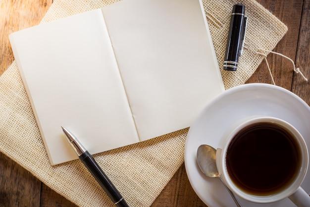 Leeres notizbuch mit stift und tasse kaffee
