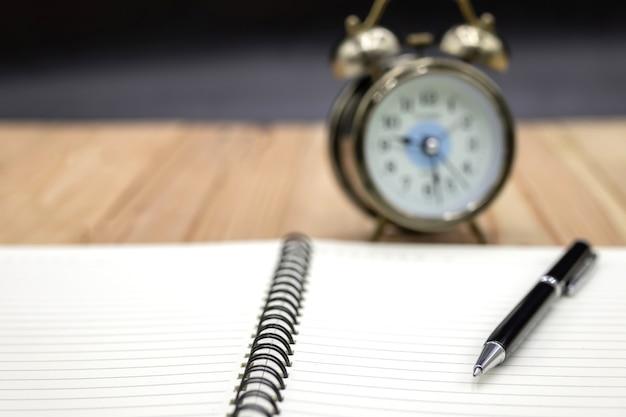 Leeres notizbuch mit stift und uhr auf dem tisch
