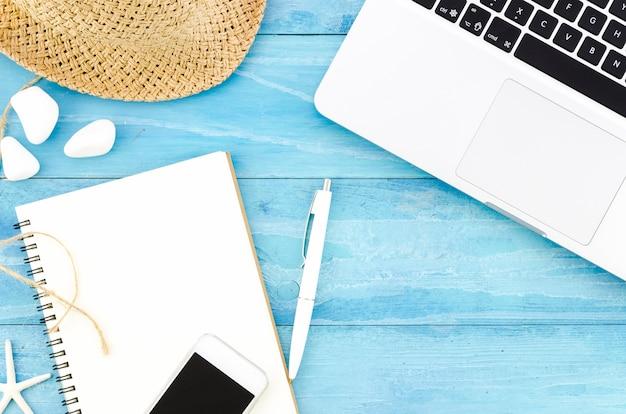 Leeres notizbuch mit strohhut und laptop