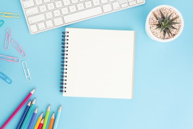 Leeres notizbuch mit tastatur und bleistift auf blau
