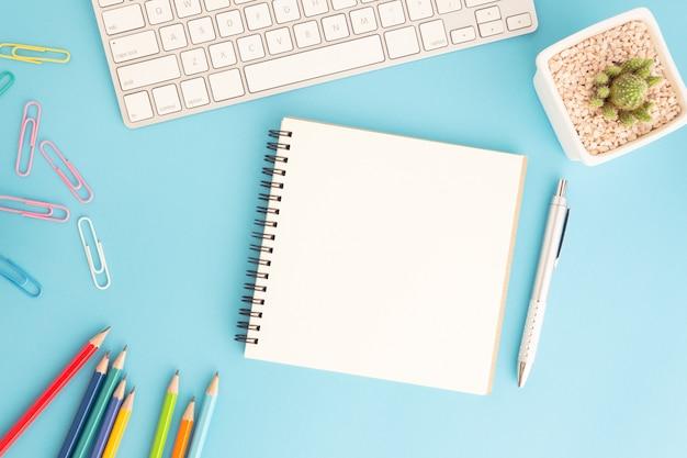 Leeres notizbuch mit tastatur und stift auf blau