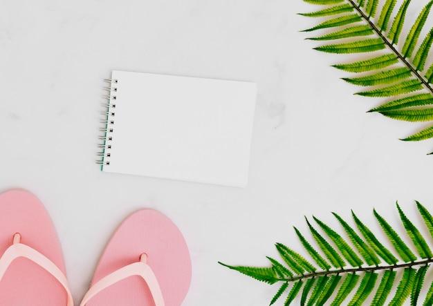 Leeres notizbuch mit tropischem palmblatt