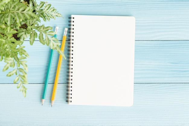 Leeres notizbuch mit und bleistift auf blauem hintergrund