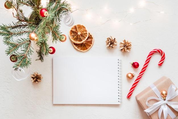Leeres notizbuch mit wunschliste und weihnachtsdekor auf weißem tisch. kopieren sie platz für grußtext oder beschriftung.