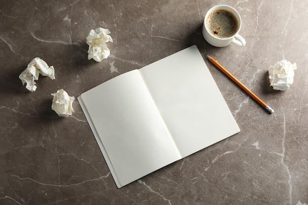 Leeres notizbuch, papierkugeln, bleistift und tasse kaffee auf grauem hintergrund, draufsicht