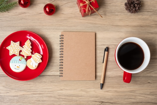 Leeres notizbuch, schwarze kaffeetasse, weihnachtsplätzchen und stift auf holztisch, draufsicht und kopienraum. weihnachten, frohes neues jahr, ziele, auflösung, aufgabenliste, strategie und plankonzept