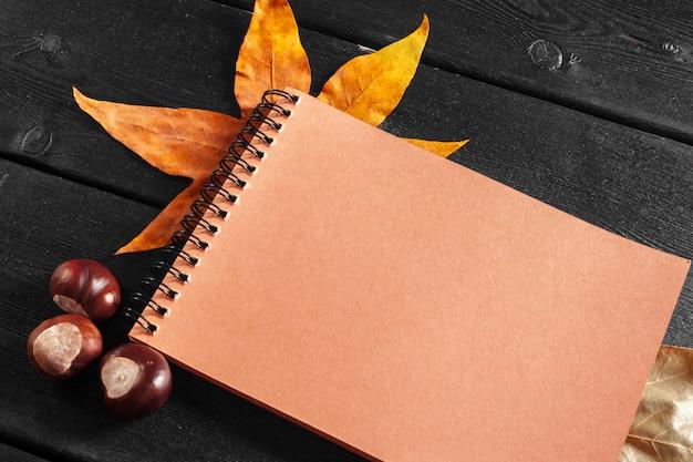 Leeres notizbuch umgeben durch herbstlaub
