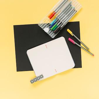 Leeres notizbuch und bunte filzstifte auf schwarzem und gelbem kartenpapierhintergrund