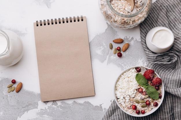 Leeres notizbuch und frühstückszutaten notizbuch und frühstückszutaten