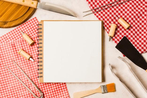 Leeres notizbuch und grillwerkzeuge