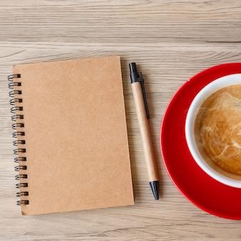 Leeres notizbuch und kaffeetasse auf holztisch. motivation, auflösung, to-do-liste, strategie und plankonzept