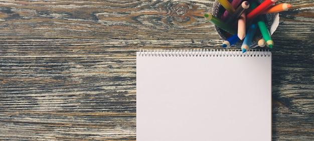 Leeres notizbuch und satz bunte stifte auf dem holztisch. papierhintergrund.