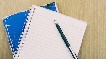 Leeres Notizbuch und schwarzer Stift auf hölzernem Schreibtisch.