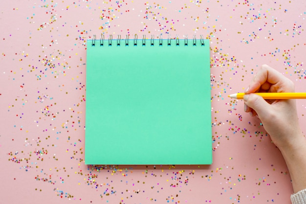 Leeres notizbuch und stift mit konfetti