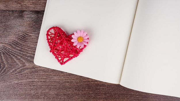 Leeres notizbuch und stift mit roter herzformdekoration auf hölzernem tischhintergrund.