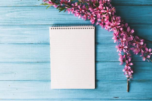 Leeres notizbuch und wilde blumen auf blauem hölzernem hintergrund. konzept blumen des frühlings,