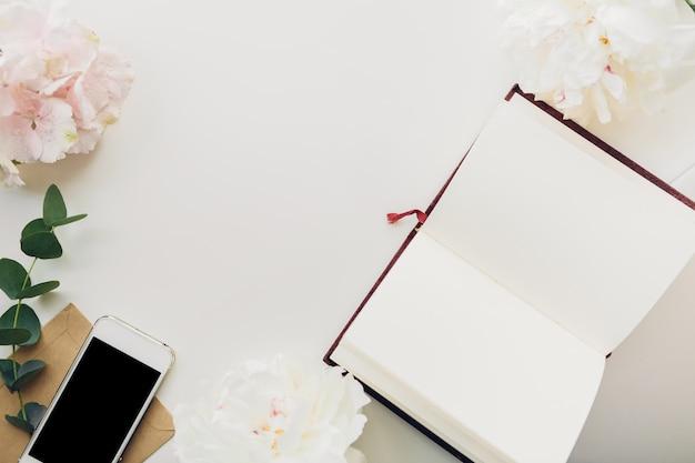 Leeres notizbuch von blumen und telefon. draufsicht. attrappe, lehrmodell, simulation