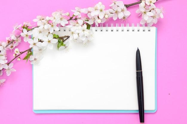Leeres notizbuchblatt mit stift und blühenden zweigen mit weißen blumen auf einem rosa hintergrund. frühlingsmodell für ihre texte