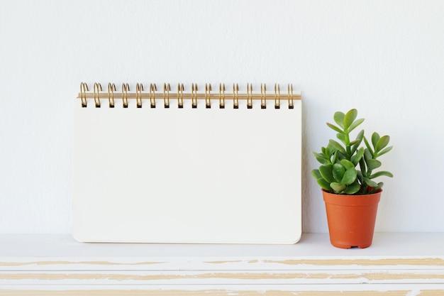Leeres notizbuchpapier auf weißem tabellenhintergrund