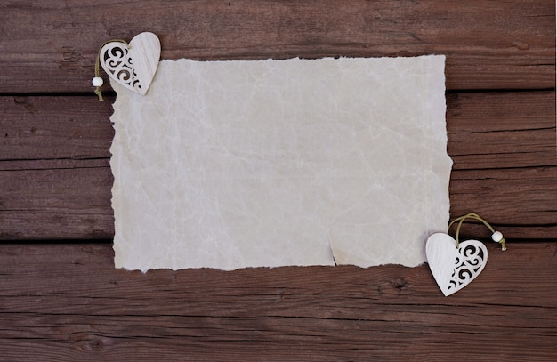 Leeres oder leeres papier mit holzherzen auf einem hölzernen hintergrund platz für textkopierraum