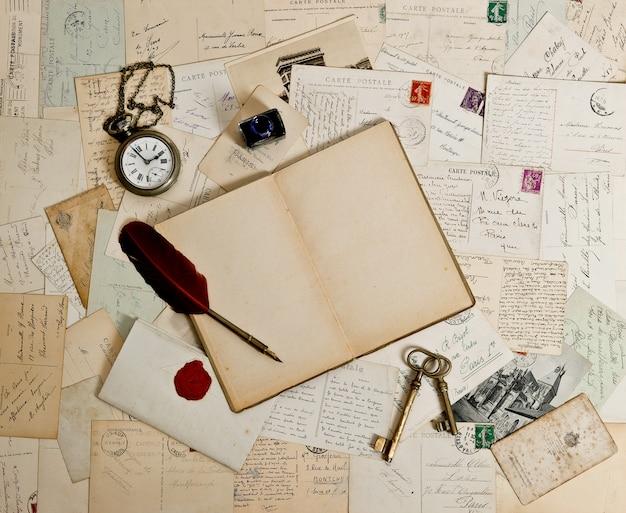Leeres offenes buch, altes zubehör und postkarten. romantischer vintage-hintergrund