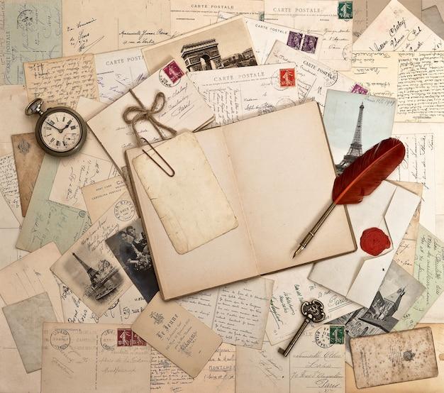 Leeres offenes buch, altes zubehör und postkarten. sentimentaler vintage-hintergrund