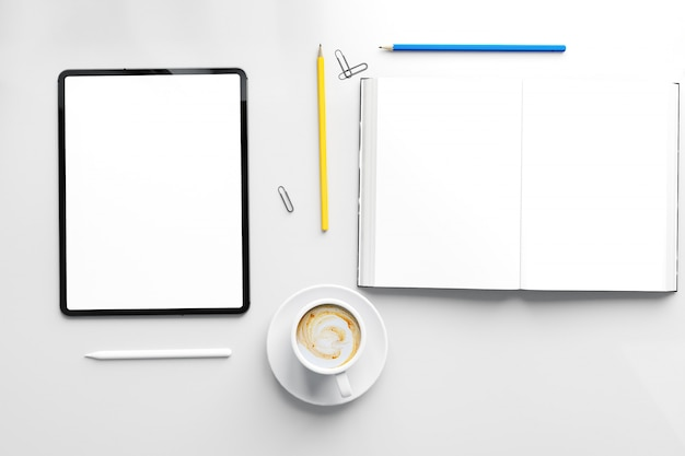 Leeres offenes buch und leerer weißer bildschirm des modernen tabletts