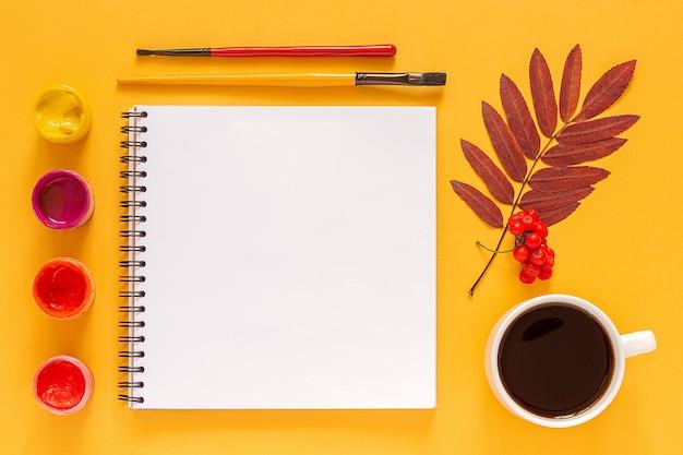 Leeres offenes einklebebuch, farbige blattherbarium- und -aquarellfarben, pinsel auf gelb. zurück zur schule