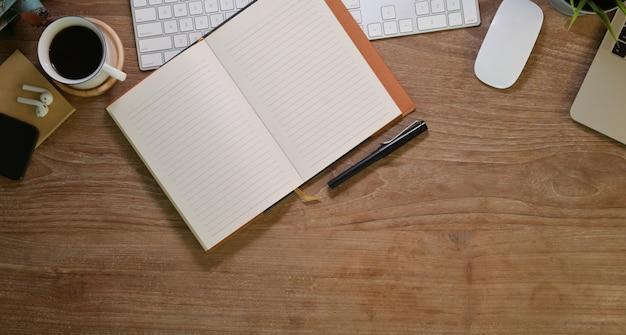 Leeres offenes notizbuch an bequemem arbeitsplatz mit büro