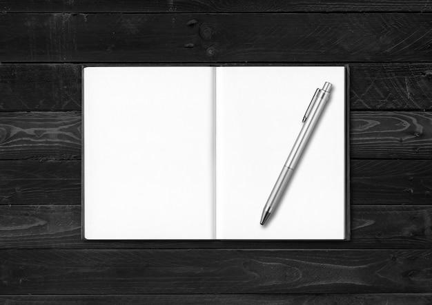 Leeres offenes notizbuch und stift lokalisiert auf schwarzem holzhintergrund