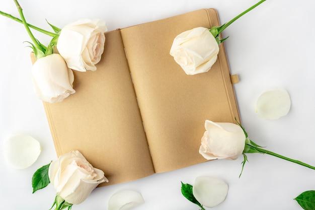 Leeres offenes tagebuch mit weißen rosen verziert