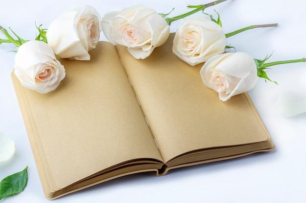 Leeres offenes tagebuch (notizbuch, skizzenbuch), verziert mit weißen rosen mit platz für text oder schrift
