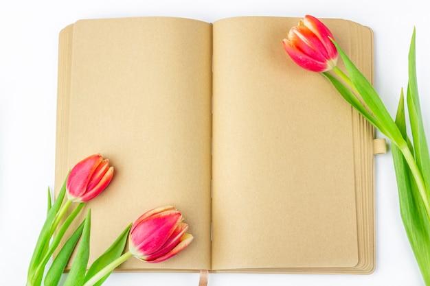 Leeres offenes tagebuch, verziert mit frühlingsroten tulpen mit platz für text oder schriftzug.