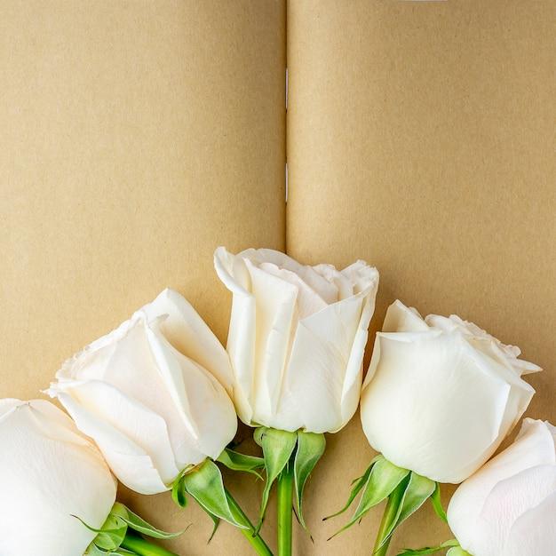 Leeres offenes tagebuch, verziert mit weißen rosen mit platz für text oder schriftzug. konzept des schreibens von briefen, wünschen, zielen, plänen, lebensgeschichte. flach gelegte modellfederzusammensetzung