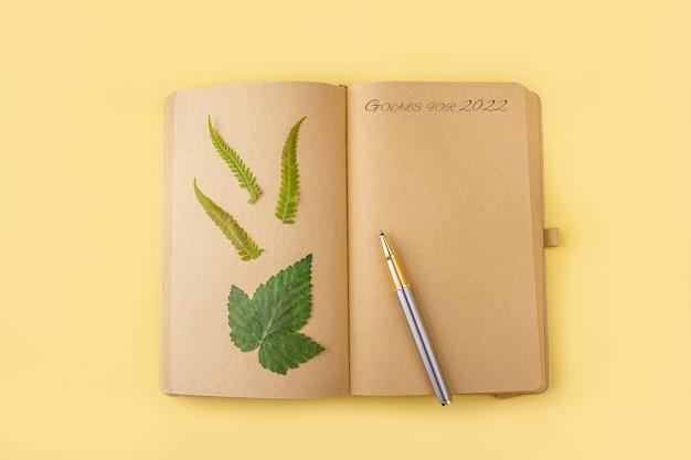 Leeres offenes vintage-tagebuch, notizbuch mit herbarium verschiedener gepresster getrockneter pflanzen und stift. wünsche schreiben, ziele für 2022, pläne, aktivitäten. botanischer satz wilder blumen, kräuter. platz für text kopieren