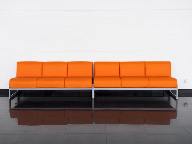 Leeres orange sofa im raum nahe weißer wand. wartehalle