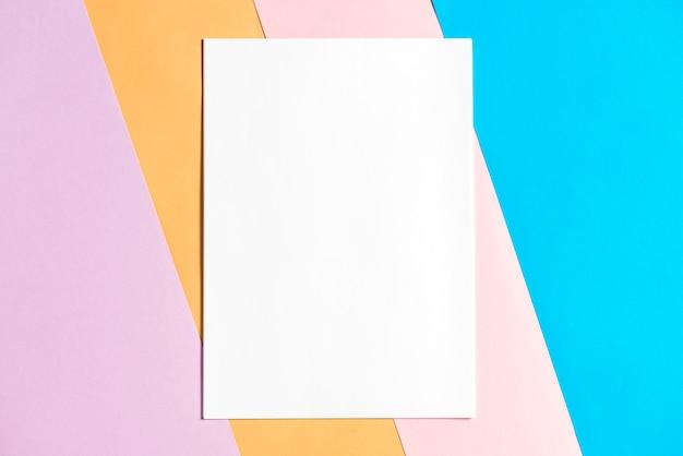 Leeres papier auf buntem papierhintergrund