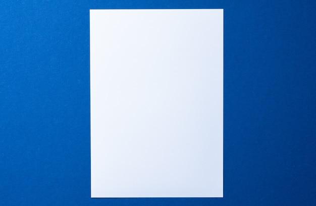 Leeres papier auf draufsicht des blauen hintergrunds