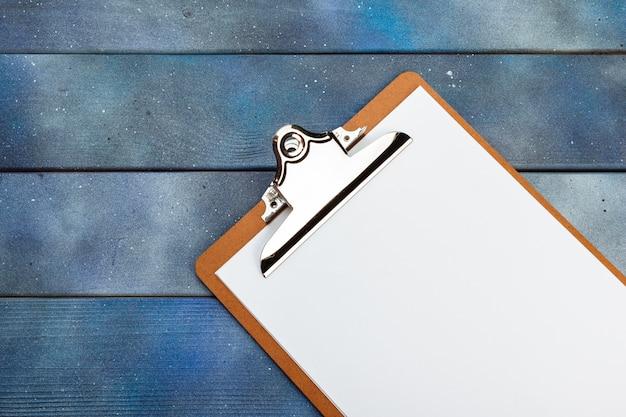 Leeres papier auf hölzernem klemmbrett auf dunklem bretterboden