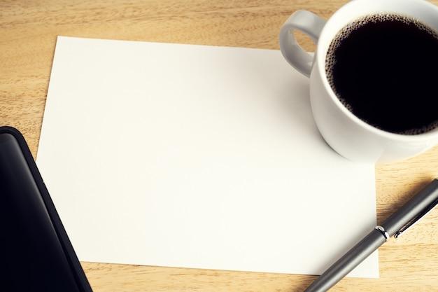 Leeres papier auf hölzernem schreibtisch tisch mit tasse kaffee, stift und smartphone. mock-up-vorlage. studien- oder geschäftskonzept
